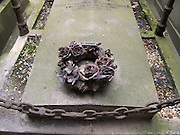 a flower wreath of stone on top of a grave