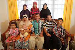 Bahagia Rahmatullah  (Rahmat) 16. 7 months and his family<br />Back row L-R: Sister Nurlia, sister Miftahul Jannah, sister Siti Arlina  <br />Front Row L-R  Nice Humairah, Mother  Wardiaty with Niece Baby Askia, Father Ilyas, nephew Fajar rullah.<br />Rahmat was photographed in 2004 at home in Lho-Nga just following by the Indian Ocean tsunami, Aceh Province, Sumatra, Indonesia.