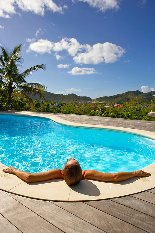 Rear view of woman relaxing in swimming pool at villa above St. Jean Bay, St. Barthelemy, FWI