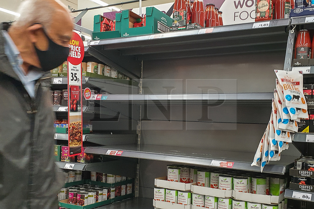 © Licensed to London News Pictures. 25/09/2020. London, UK. A shopper wearing a face mask walks past empty shelves in Morrisons supermarket in north London as essential items start to run out amidst a possible second lockdown due to a rise in COVID-19 cases. A number of supermarkets are restricting shoppers from bulk-buying products such as flour, pasta, toilet rolls and anti-bacterial wipes. Photo credit: Dinendra Haria/LNP