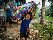 26 OCTOBER 2016 - NUPO TEMPORARY SHELTER, MAE CHAN, TAK, THAILAND:  A Burmese refugee in the Nupo Temporary Shelter refugee camp walks to waiting buses before their repatriation Wednesday. Sixtyfive Burmese refugees living in the Nupo Temporary Shelter refugee camp in Tak Province of Thailand were voluntarily repatriated to Myanmar. About 11,000 people live in the camp. The repatriation was the first large scale repatriation of Myanmar refugees living in Thailand. Government officials on both sides of the Thai / Myanmar border said the repatriation was made possible by recent democratic reforms in Myanmar. There are approximately 150,000 Burmese refugees living in camps along the Thai / Myanmar border. The Thai government has expressed interest several times in the last two years in starting the process of repatriating the refugees.    PHOTO BY JACK KURTZ