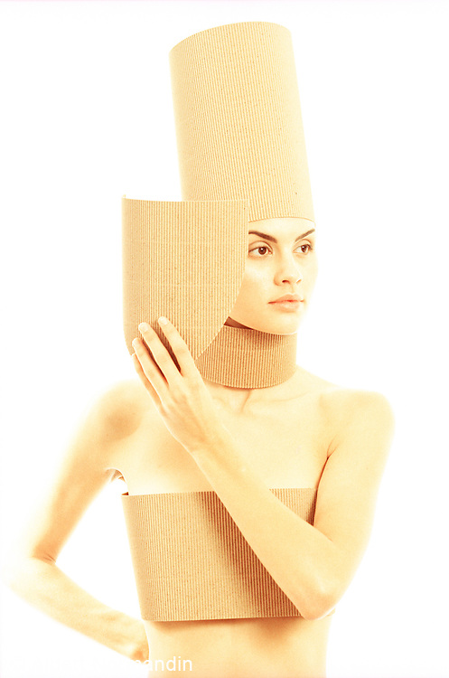 Portrait of woman covered corrugated cardboard looking away