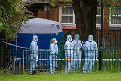 © Licensed to London News Pictures. 04/07/2020. London, UK. Investigators stand next to a forensic tent on Westbourne Estate in Islington. Metropolitan Police Service officers were called at 15:20BST on Saturday, 4 July to Roman Way N7 following reports of shots fired. Officers attended with London Ambulance Service (LAS) and found a man, believed to be aged in his early 20s, suffering from gunshot injuries. Despite their best efforts, he was pronounced dead at the scene. Photo credit: Peter Manning/LNP