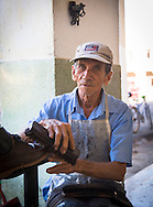 Shooshiner polishing shoes on sidewalk, Caibarién, Cuba