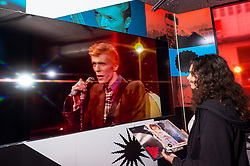 © Licensed to London News Pictures. 25/10/2021. LONDON, UK. Bowie fan, Farida Doss, views a video screen at the opening of a David Bowie pop-up shop in Heddon Street in the West End.  Open 75 days before the late singer's 75th birthday, the pop-up is located close to where Bowie posed as Ziggy Stardust on the cover of his 1972 album The Rise and Fall of Ziggy Stardust and the Spider from Mars.  The store sells limited edition records and memorabilia curated by his estate and will be open until January 2022. A sister shop will open in New York and both form part of a year long celebration of David Bowie's 75th birthday.  Photo credit: Stephen Chung/LNP