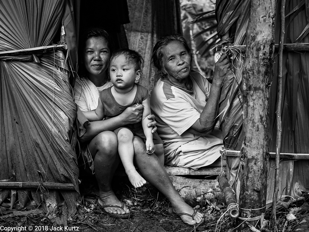 26 JANUARY 2018 - SANTO DOMINGO, ALBAY, PHILIPPINES: People evacuated from the slopes of the Mayon volcano in an impromptu shelter they built on the side of the Legazpi - Tabaco Road, which runs through Santo Domingo. The volcano was relatively quiet Friday, but the number of evacuees swelled to nearly 80,000 as people left the side of  the volcano in search of safety. There are nearly 12,000 evacuees in Santo Domingo, one of the communities most impacted by the volcano. The number of evacuees is impacting the availability of shelter space. Many people in Santo Domingo, on the north side of the volcano, are sleeping in huts made from bamboo and plastic sheeting. The Philippines is now preparing to house the volcano evacuees for up to three months.      PHOTO BY JACK KURTZ