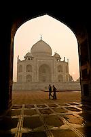 A couple walk round the Taj Mahal just after sunrise in Agra, Uttar Pradesh, India