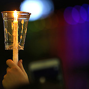 A candle is seen during a vigil held at the Dr. Phillips Center for the Performing Arts for the victims of a mass shooting at the Pulse nightclub Monday, June 13, 2016, in Orlando, Florida.  A gunman killed dozens of people in a massacre at the crowded gay nightclub in Orlando on Sunday, making it the deadliest mass shooting in modern U.S. history. (Alex Menendez via AP)