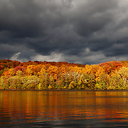 """""""Storm""""-5<br /> <br /> Enjoy amazing reflections of fall foliage on the Huron River! A glimmer of sunshine comes through dark and stormy clouds to create a beautiful autumn image!!<br /> <br /> Autumn Landscapes by Rachel Cohen"""