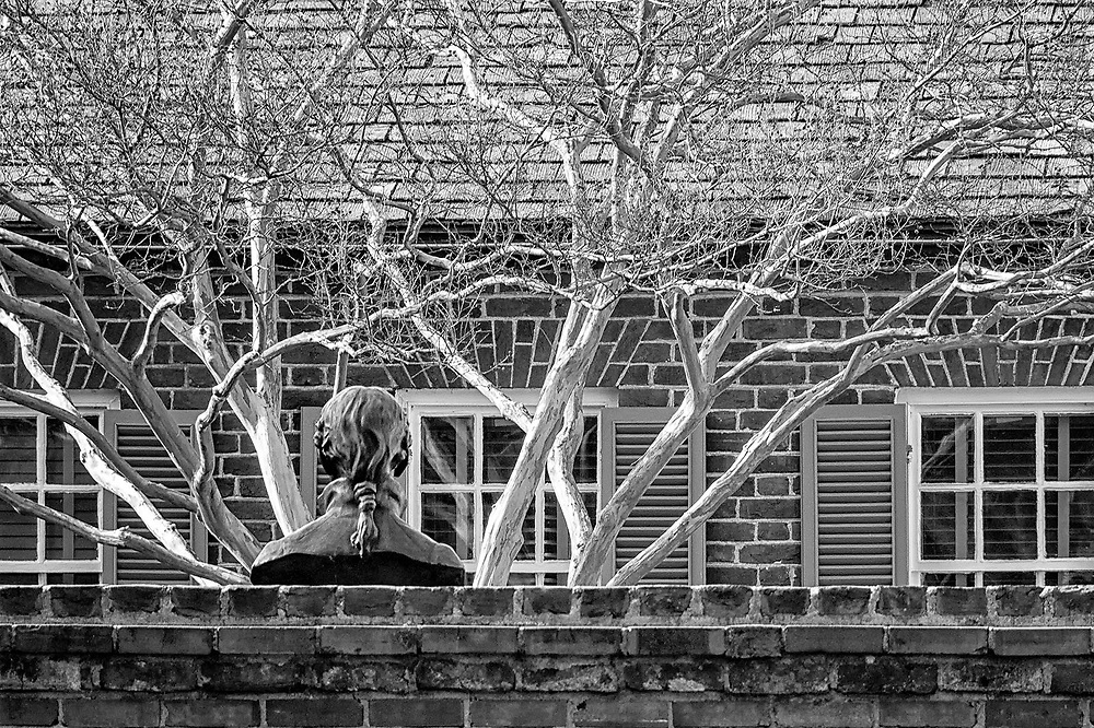 Seen from across a brick wall, a bust of James Monroe, Founding Father who served as America's fifth President, occupies a courtyard.