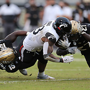 ORLANDO, FL - NOVEMBER 21:  Tatum Bethune #15 of the Central Florida Knights and Richie Grant #27 of the Central Florida Knights stop Gerrid Doaks #23 of the Cincinnati Bearcats at Bounce House-FBC Mortgage Field on November 21, 2020 in Orlando, Florida. (Photo by Alex Menendez/Getty Images) *** Local Caption *** Tatum Bethune;Richie Grant; Gerrid Doaks