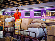 02 JANUARY 2019 - BANGKOK, THAILAND:      A worker takes parcels to a train in Hua Lamphong Train Station in Bangkok. The train and bus stations in Bangkok were crowded Wednesday with people going home after the long New Year's weekend.     PHOTO BY JACK KURTZ
