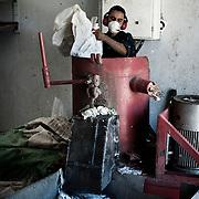 """Trabajador """"Zabbaleen"""" en una de las máquinas que tritura plástico para su reutilización en la planta de reciclaje de Katameya, que dirige la ONG A.P.E. en las afueras del Cairo. En medio del barrio de Manshiet Nasr a las afueras de El Cairo esta situado el asentamiento de Mokattam conocido como la """"Ciudad de la Basura"""" , está habitado por los Zabbaleen ,una comunidad de unos 45.000 cristianos coptos que viven desde hace varias décadas de reciclar los desperdicios que genera la capital egipcia: plástico, aluminio, papel y desechos órganicos que transforman en compost . La mayoría forman parte de la Asociación para la Protección del Ambiente (APE) una ONG que actúa en el área, cuyos objetivos son proteger el medio ambiente y aumentar el sustento de las recuperadores de basura de El Cairo. Según la ONU, el trabajo que se realiza en Mokattam como uno de los diez mejores ejemplos del mundo en el mejoramiento medioambiental. El Cairo , Egipto, Junio 2011. ( Foto : Jordi Camí )"""