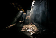 Migrants walking between two warehouses in a makeshift camp in an old train depot in Belgrade, Serbia. 15th January 2017. Federico Scoppa