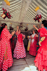 Europe, Spain, Sevilla (also known as Seville), women in flamenco dresses dancing at annual Feria de Abril festival