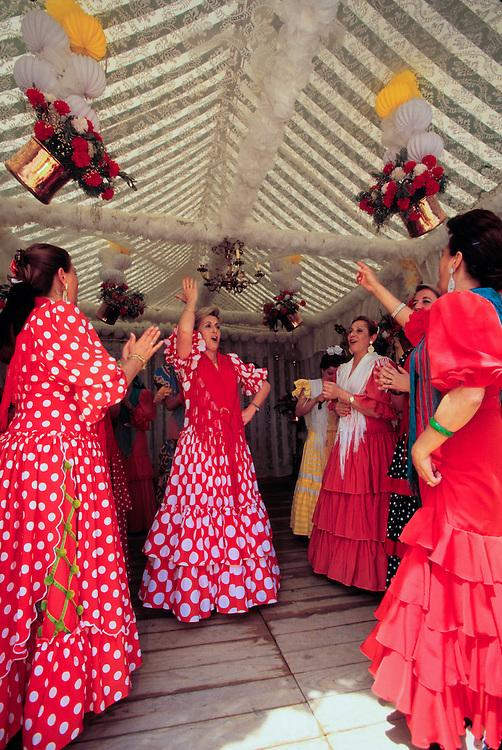 Europe, Spain, Sevilla (also known as Seville), women in flamenco dresses dancing at annual Feria de Abril festival