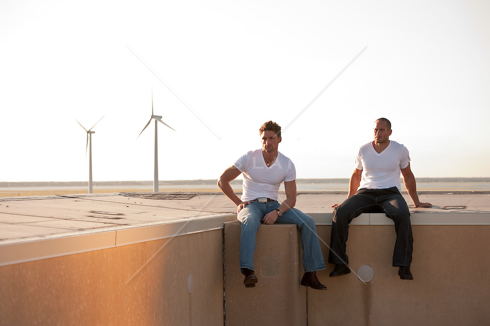 two men seated on a roof top in Atlantic City, NJ with windmills in the background