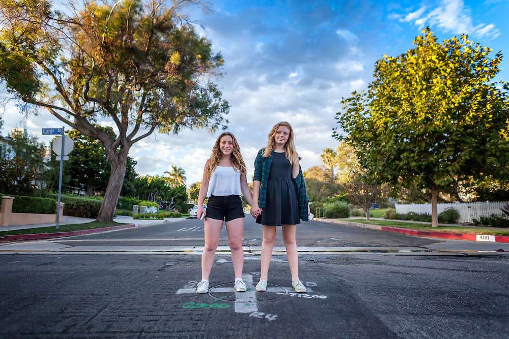 """Natalie Schoemann and Katie Duke hold hands at the intersection of Via de la Paz and Friends Street in the idyllic neighborhood near """"the Bluffs"""" in Pacific Palisades, California."""