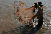 Cambodian man net fishing on the Tonle Sap Lake, an estuary of the Mekong River near Siem Reap.