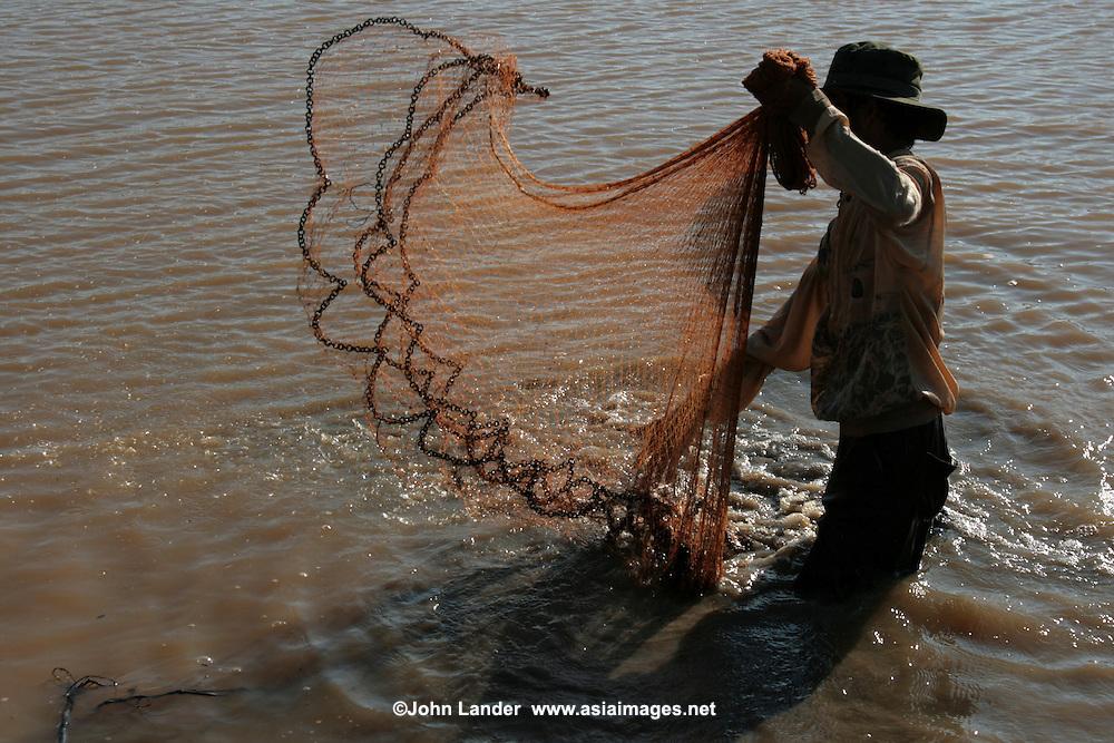 Cambodian man net fishing on the Tonle Sap Lake, an estuary of the Mekong River near Siem Reap.