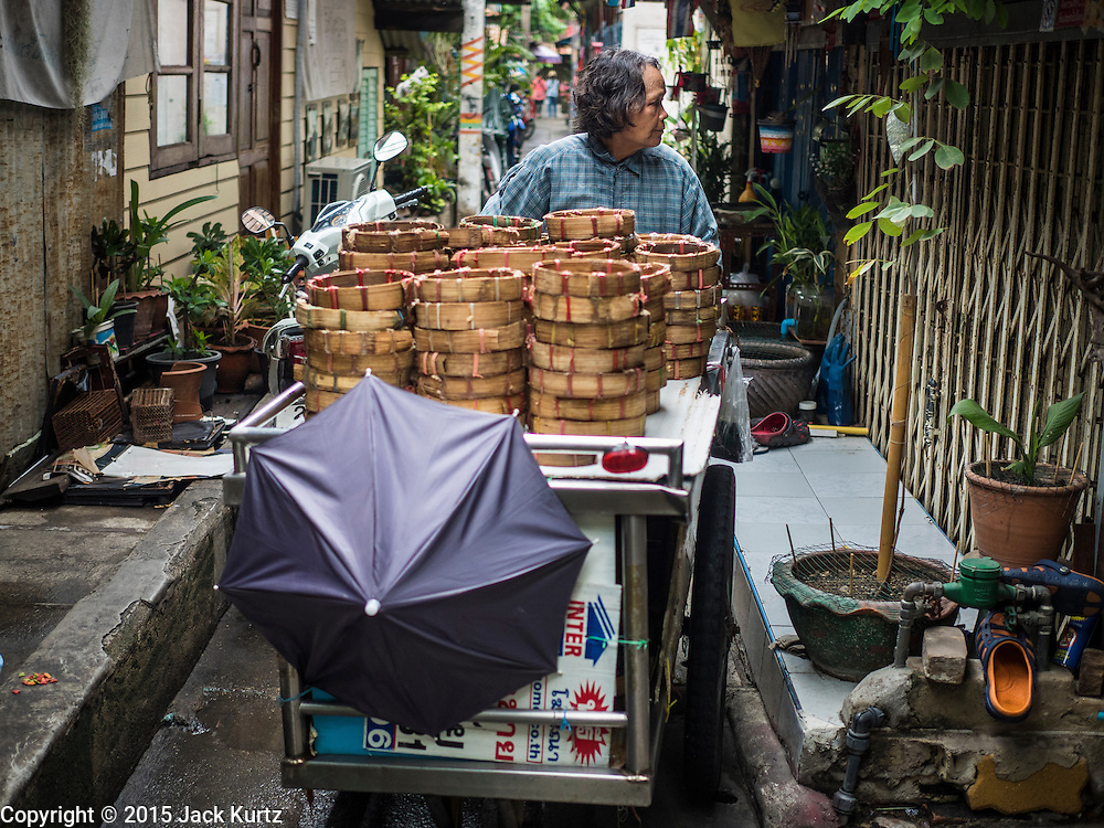 28 SEPTEMBER 2015 - BANGKOK, THAILAND:  A fish monger pushes her cart through the Wat Kalayanamit neighborhood. Fifty-four homes around Wat Kalayanamit, a historic Buddhist temple on the Chao Phraya River in the Thonburi section of Bangkok, are being razed and the residents evicted to make way for new development at the temple. The abbot of the temple said he was evicting the residents, who have lived on the temple grounds for generations, because their homes are unsafe and because he wants to improve the temple grounds. The evictions are a part of a Bangkok trend, especially along the Chao Phraya River and BTS light rail lines. Low income people are being evicted from their long time homes to make way for urban renewal.   PHOTO BY JACK KURTZ