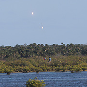 In this image taken from inside the Merritt Island National Wildlife Refuge, the SpaceX Falcon Heavy rocket boosters return to the Kennedy Space Center after its inaugural test flight on Tuesday, February 6 2018 in Titusville, Florida. The high-power launcher also boosted Elon Musk's electric Tesla sportswear into deep space. (Alex Menendez via AP)