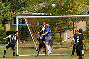 Ivan Rodriguez (center in black) of Deportivo Colomex defends his goal against Team Shlama F.C. during National Soccer League play in Skokie, Il.