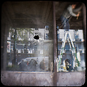 The reflection of Hotel Grande Bretagne on a broken window pane of a bank on Panapistimiou street. <br /> <br /> Following the murder of a 15 year old boy, Alexandros Grigoropoulos, by a policeman on 6 December 2008 widespread riots, protests and unrest followed lasting for several weeks and spreading beyond the capital and even overseas<br /> <br /> When I walked in the streets of my town the day after the riots I instantly forgot the image I had about Athens, that of a bustling, peaceful, energetic metropolis and in my mind came the old photographs from WWII, the civil war and the students uprising against the dictatorship. <br /> <br /> Thus I decided not to turn my digital camera straight to the destroyed buildings but to photograph through an old camera that worked as a filter, a barrier between me and the city.