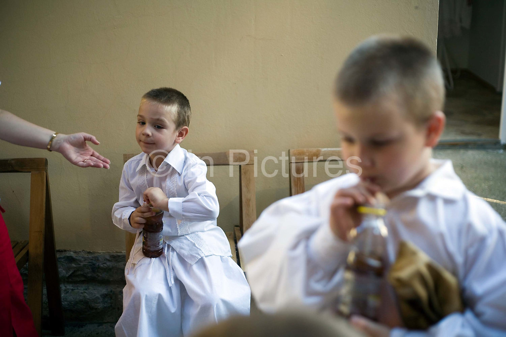 Boys backstage in traditional costume drink soda from bottles during a folk event in Pecs, Hungary.Pecs has been chosen as the 2010 European City of Culture. The city is on the southern slopes of the Mecsek Hills and has a sub-Mediterranean climate. Settled by Romans as Sopianae, it was a significant Christian settlement. Later conquered by the Ottomans, it has important Turkish architecture.