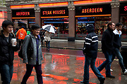 Aberdeen Steak Houses lights reflected in the wet pavement in London. Aberdeen Angus Steak Houses is a restaurant chain of steak houses in central London. Outlets trade as Angus Steak House or Aberdeen Steak House and cater mainly for tourists. In 2001, there were about 30 outlets; about four remain open in 2010.