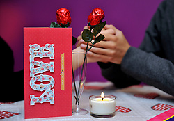 PICTURE POSED BY MODELS Stock photo of a couple with valentines gifts of a card, chocolates and chocolate roses in a glass in time for St Valentine's Day on February 14.