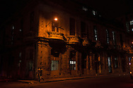 Two men walking at night round a corner in Centro Habana, one of the 15 municipalities or boroughs in Havana, Cuba.