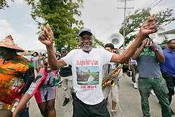 29 August 2015. Lower 9th Ward, New Orleans, Louisiana.<br /> Hurricane Katrina 10th anniversary memorials.  <br /> Robert Green, an original Rooftop Rider and survivor of the storm dances in a second line parade to remember those who perished and to celebrate the survivors. Green lost his mother and grand daughter to the storm. Photo credit©; Charlie Varley/varleypix.com.