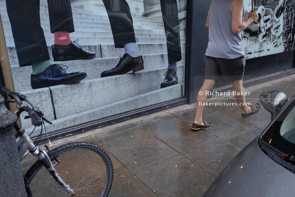 A man strides past the shoes, socks and legs  in the window of a menswear retailer on the Kings Road in Chelsea, on 24th August 2020, in London, England.