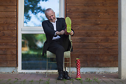 Senior businessman wearing suit and putting wellington boot, Freiburg im Breisgau, Baden-Wuerttemberg, Germany