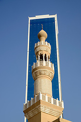 Modern skyscraper and contrasting mosque minaret  in  Dubai United Arab Emirates