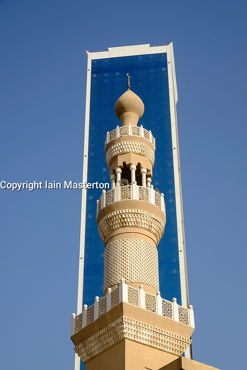 Modern skyscraper and contrasting mosque minaret  in  Dubai United Arab Emirates