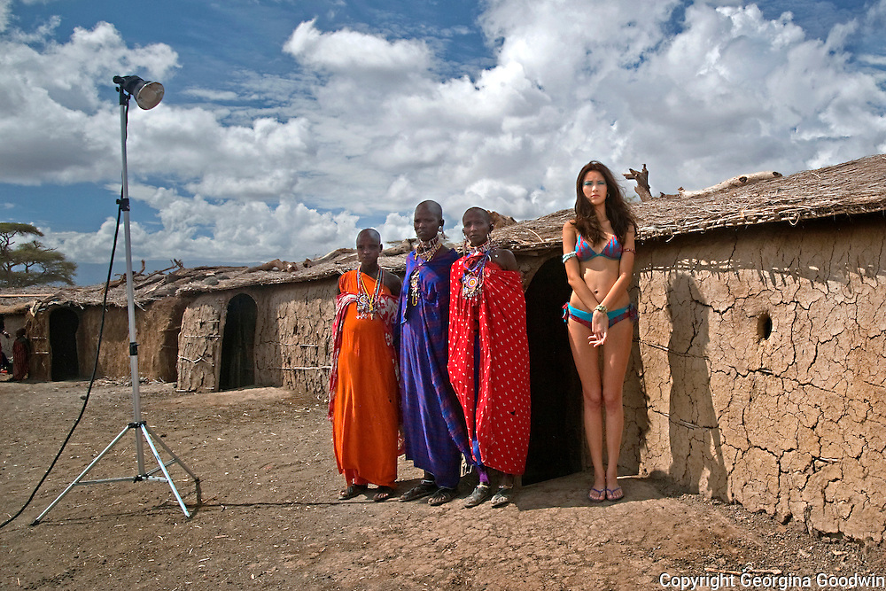 Benedetta (21) a model from Italy, poses for a swimwear catalogue shoot against a backdrop of women from the Masai tribe located in Amboseli National Park dressed in traditional clothes, compounding the lightyears of cultural differences between these women. January 2009