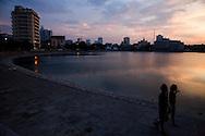 A couple walks alongside Giang Vo lake at sunset, Hanoi, Vietnam, Southeast Asia
