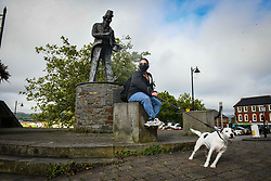 © Licensed to London News Pictures. 08/09/2020. Caerphilly, Wales, UK. Resident, Claire Evans sits by the Tommy Cooper statue in the town of Caerphilly in south Wales, which has gone into lockdown along with it's wider borough area, after what is being described as a rapid increase in coronavirus cases. The Welsh government announced that from 6pm on Tuesday people will not be able to leave or enter the area without good reason, along with other restrictive measures.<br />  Photo credit: Robert Melen/LNP