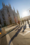 People are silhouetted by the low winter sun front of the Cathedral in Piazza del Duomo, central Milan on 7th December 2008 in Milan, Italy. The cathedral, or duomo took six centuries to build, occupies the heart of the city, and attracts visitors from all over the world.