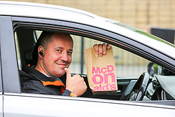 © Licensed to London News Pictures. 04/06/2020. London, UK. A man holds a bag of McDonald's meal and gives a thumbs up after leaving McDonald's Drive Thru in north London. McDonald's Drive Thru opens in Haringey after lockdown restrictions are relaxed. Photo credit: Dinendra Haria/LNP
