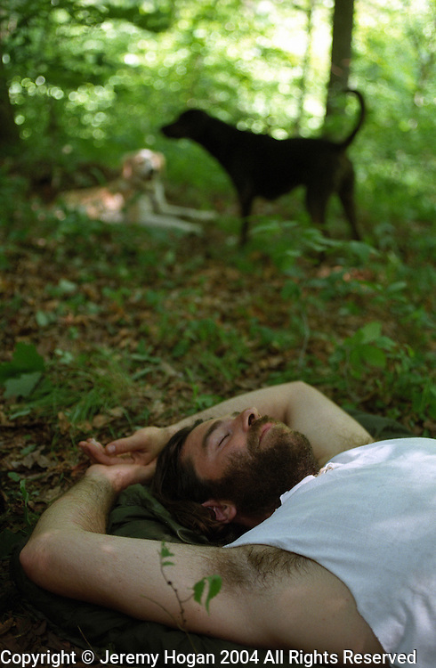 Photo by Jeremy Hogan..man relaxing in forest with dogs, genx, generation x, hip, hipster, nature, napping, vertical, color,