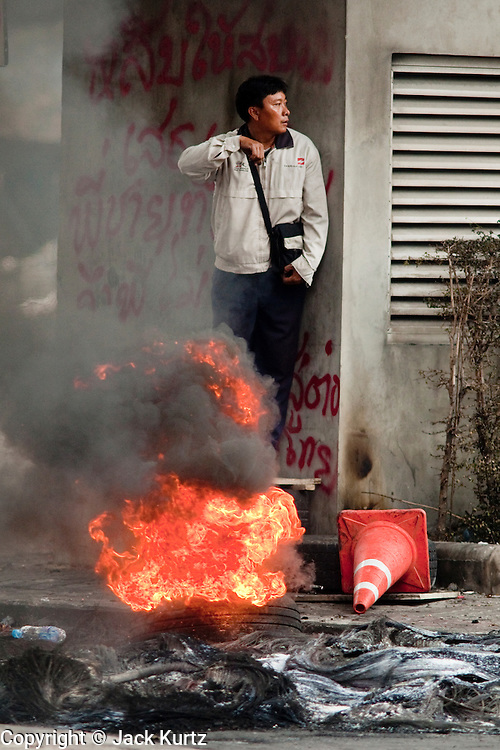 18 MAY 2010 - BANGKOK, THAILAND:  A man looks for snipers before crossing past a burning tire at Din Daeng Intersection in Bangkok Tuesday. The intersection has been under periodic sniper fire from unidentified snipers near Thai military lines. Violent unrest continued in Bangkok again Tuesday nearly a week after Thai troops started firing on protesters and Bangkok residents took to the streets in violent protest against the government. Tuesday was not as violent as previous days however. Although protesters continued to set up roadblocks and flaming tire barricades across parts of the city, there was not as much gunfire from the government lines. The most active protesters were at the Din Daeng Intersection about a mile from the Red Shirts' Ratchaprasong camp.  PHOTO BY JACK KURTZ