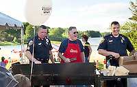 Sgt. Gary Hubbard, Steve Hooper and Lt. Matt Canfield cook up some hotdogs on the grill for Laconia Police Department's Block Party at Opechee Cove in conjunction with National Night Out Tuesday evening.  (Karen Bobotas/for the Laconia Daily Sun)