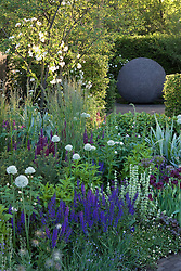 The Bupa Garden. Large spherical sculpture of textured concrete acting as focal point. Foreground planting includes Allium nigrum and Calamagrostis x acutiflora 'Karl Foerster'. Design: Cleve West, Bupa Garden, Chelsea 2008