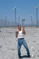 Man outdoors tossing large rocks  by Palm Springs windmills