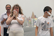 Moscow, Russia, 07/08/2010. .A woman in Red Square chokes on the worst smog so far in the record high temperatures of the continuing heatwave. Peat and forest fires in the countryside surrounding Moscow have resulted in the Russian capital being blanketed in heavy smog.