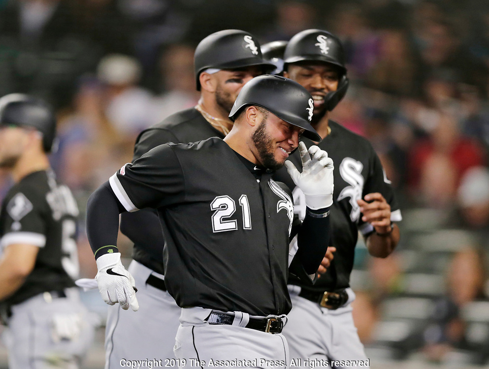 Chicago White Sox's Welington Castillo runs to the dugout leading teammates Yoan Moncada, Eloy Jimenez, and Eloy Jimenez who scored on his grand slam hit on a pitch from Seattle Mariners' Brandon Brennan  during the fifth inning of a baseball game, Sunday, Sept. 15, 2019, in Seattle. (AP Photo/John Froschauer)