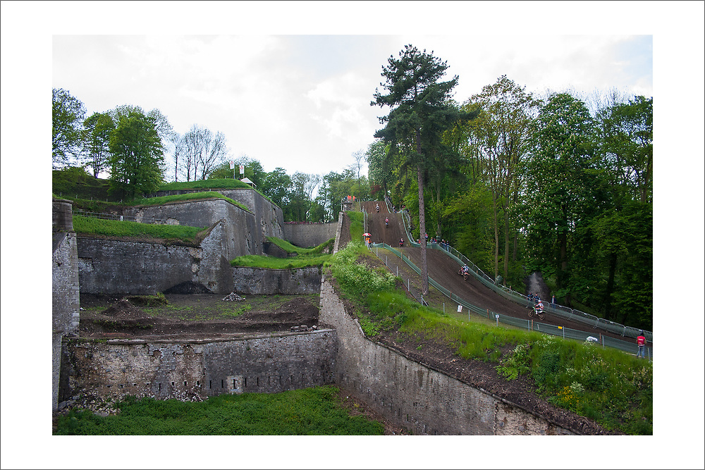 This print is of the famous Namur track in the town of the same name. Since the 1940's Namur has made it off and on the GP circuit with mixed reviews from riders. I think it is the kind of place you love or hate. As a photographer, I love it. As a rider, I think I would also like it since it is part motocross, part trail riding, or cross country. The start area is located at the top of Namur, an area called the Citadel. In this photo the riders are climbing up from the bottom of the track (near Carla's famous Cafe) toward the Citadel. <br /> <br /> This photo was shot in 2006, the second year I went to Namur. After my first trip, I was annoyed my photos did not really capture the character and scale of the facility, nor did they reveal the military history of the place. This photo meant to change that. <br /> <br /> © Roddy MacLeod Photography